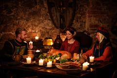 Medieval people eat and drink in ancient castle kitchen interior Stock Photos