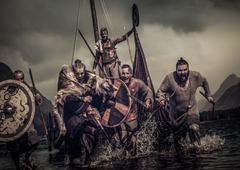 Mad vikings warriors in attack, running along shore with Drakkar on background Stock Photos
