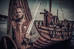 Viking warrior with sword and shield standing near Drakkar on seashore Stock Photos