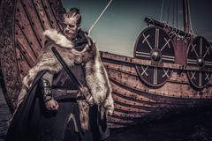 Viking warrior with sword standing near Drakkar on seashore Stock Photos