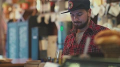 Portrait of a young man with a beard, wearing a cap and a red plaid shirt Stock Footage