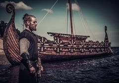 Viking warrior standing near Drakkar on seashore Stock Photos