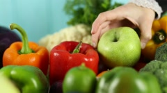 Woman puts pepper and apple on the table Stock Footage
