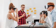 Business people using virtual reality goggles during meeting Stock Photos