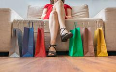 Shopping and consumerism concept. Legs of young woman sitting on sofa and man Stock Photos