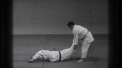1971: two people practicing self defense moves on a mat TOKYO JAPAN Stock Footage