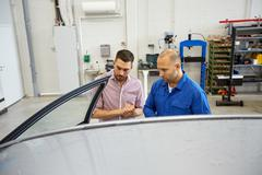 Auto mechanic and man at car shop Kuvituskuvat