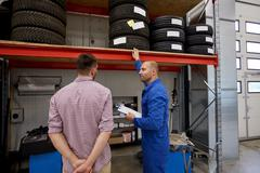 Auto mechanic and man with tires at car shop Kuvituskuvat