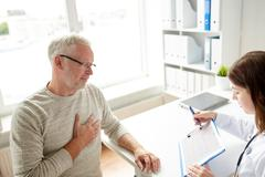 Doctor showing cardiogram to old man at hospital Stock Photos