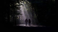 Couple walking the dog in dark forest Stock Footage