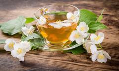 Herbal tea with jasmine flowers on rustic table Stock Photos