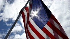 Birds flying over waving flag of United state of America - sunny cloudy blue sky Stock Footage