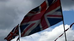 Sun, ray of light behind waving flag of Great Britain UK with a cloudy white sky Stock Footage