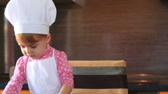 Little cute girl in chef suit playing with the dishes in the kitchen Stock Footage