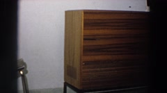 1958: figures are displayed on far end of wood storage cabinet Stock Footage
