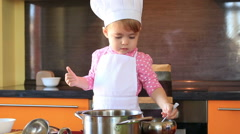 Small charming child in chef suit sprinkles sugar food in the kitchen Stock Footage