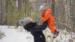 Mother playing with baby in winter Park Stock Footage