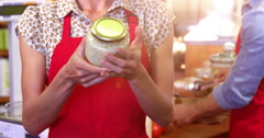 Smiling female staff holding jar in supermarket Stock Footage