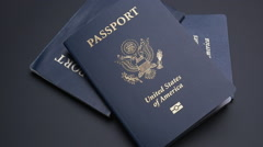 UNITED STATES PASSPORTS DROP INTO FRAME IN SLOW MOTION Stock Footage