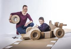 Cardboard racing car and happy family Stock Photos