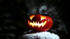 Halloween pumpkins in the winter snowy night with overflying ghost. Looped. 4K Stock Footage