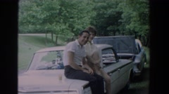 1965: husband and wife sitting on the trunk of their parked car. FALLSTON Stock Footage