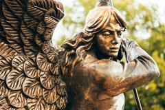 Statue Of Archangel Michael With Outstretched Wings Before Red Catholic Church Stock Photos