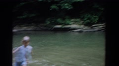 1965: kids splash, wade, and swim in local watering hole FALLSTON MARYLAND Stock Footage
