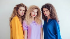 Fashion girls with professional makeup and crazy hair style, posing over white Stock Footage