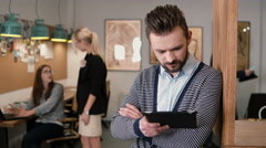 Young handsome bearded man uses touchscreen tablet in the modern startup office Stock Footage