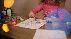 Cheerful girl draws a painting of Santa Claus in the light of Christmas lights Stock Footage
