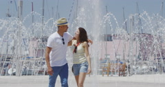 4K Happy affectionate couple cooling off at water fountain in the city Stock Footage