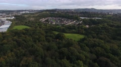 Aerial view of a housing estate surrounded by forest in the UK. Stock Footage