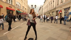 Happy girl dancing on the square in Stock Footage