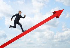 Businessman running up the big red arrow on the background of the blue sky Stock Photos