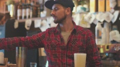 The bartender pours a cocktail into the glass and insert the straws Stock Footage