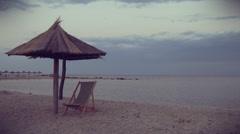 Single beach chair and umbrella near seashore Stock Footage