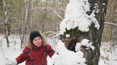 Kid playing throwing snowballs from behind tree in winter Park Stock Footage