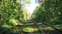Red vintage streetcar moving along tracks in green forest, beautiful nature Stock Footage