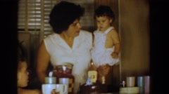 1960: a woman holding a baby at the dinner table BEL AIR MARYLAND Stock Footage
