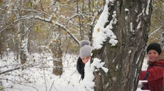 Family playing by throwing snowballs from behind tree in the winter Park Stock Footage