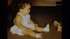1960: a awesome baby wearing white dress sitting on the ground and playing  Stock Footage
