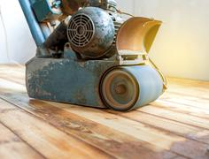 Worker polishing parquet floor with grinding machine Stock Photos