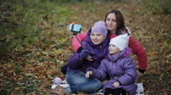 Mother and daughter are doing selfie and grimace in the autumn park Stock Footage