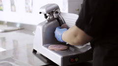 Slice machine cuts ham in commercial kitchen Stock Footage