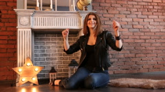The girl in black leather jackets sitting on the floor and dancing Stock Footage