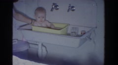1965: baby getting bathed by an adult in a little tub FALLSTON MARYLAND Stock Footage