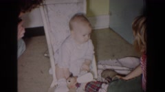 1965: baby looking at family members sitting with toys inside a room FALLSTON Stock Footage