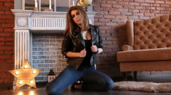 The girl in black leather jackets posing sitting on the floor Stock Footage