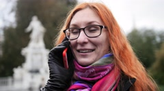 Pretty attractive young woman with red hair and glasses emotionally talking on Stock Footage